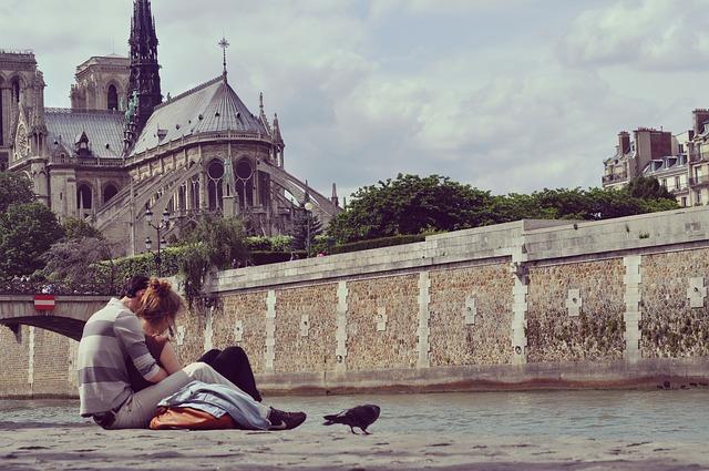 Venku na ulici na betonu sedí mladý pár, kolem nich jsou holubi a opodál katedrála